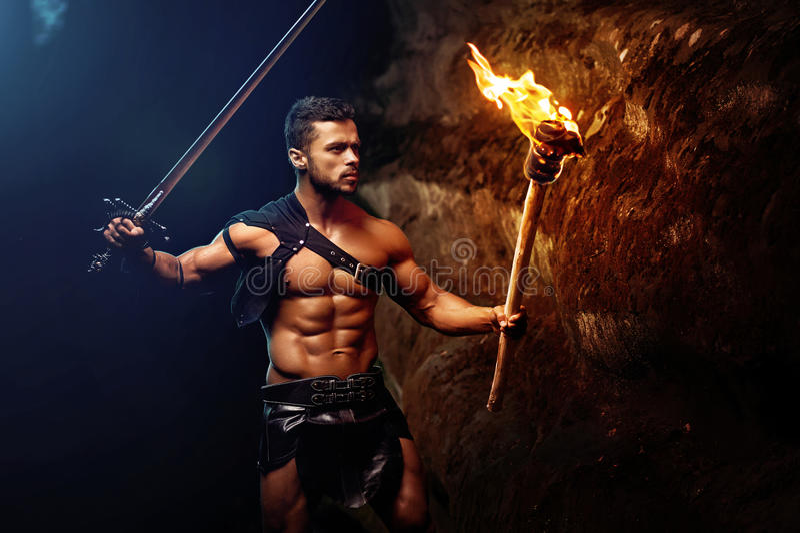 Jeune guerrier musculaire courageux avec une torche dans l'obscurité photographie stock libre de droits
