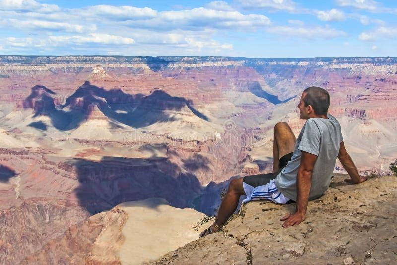 Jeune Guy Sitting au bord de Grand Canyon photographie stock libre de droits