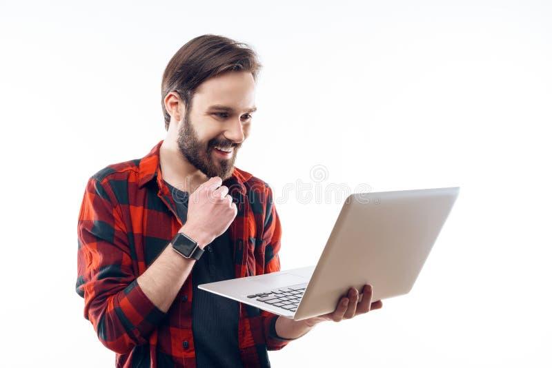 Jeune Guy Working barbu heureux de sourire sur l'ordinateur portable photos stock