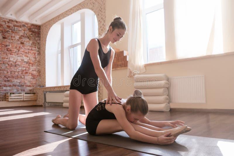 Jeune gymnastique de ballerines Aide d'amitié photo libre de droits