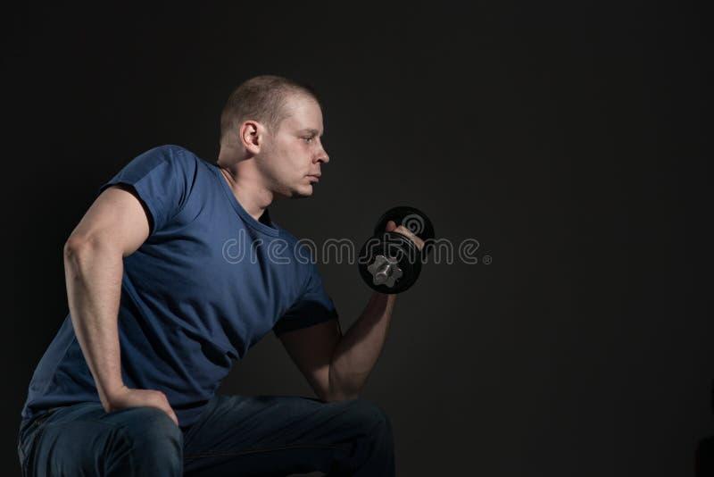 Jeune haltère mâle entre ses mains photo stock
