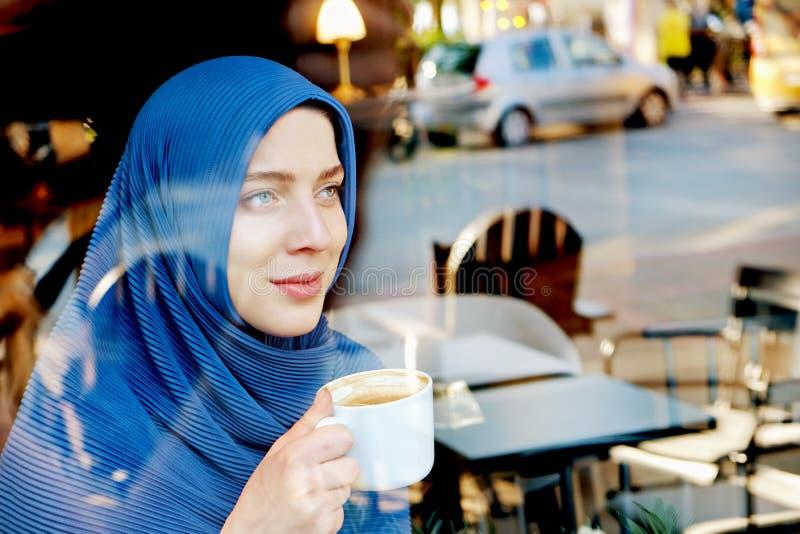 Jeune hijab de port de femme musulmane observ? par bleu photographie stock libre de droits