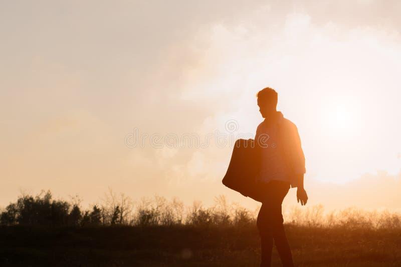 Jeune hippie avec la valise à disposition au coucher du soleil images libres de droits