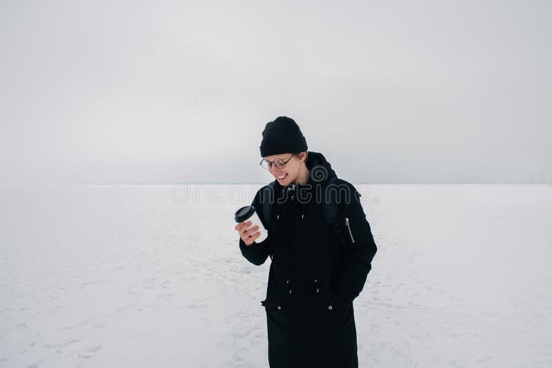 Jeune hippie de sourire de type dans le noir sur l'étang congelé couvert de neige blanc avec une tasse de café image libre de droits