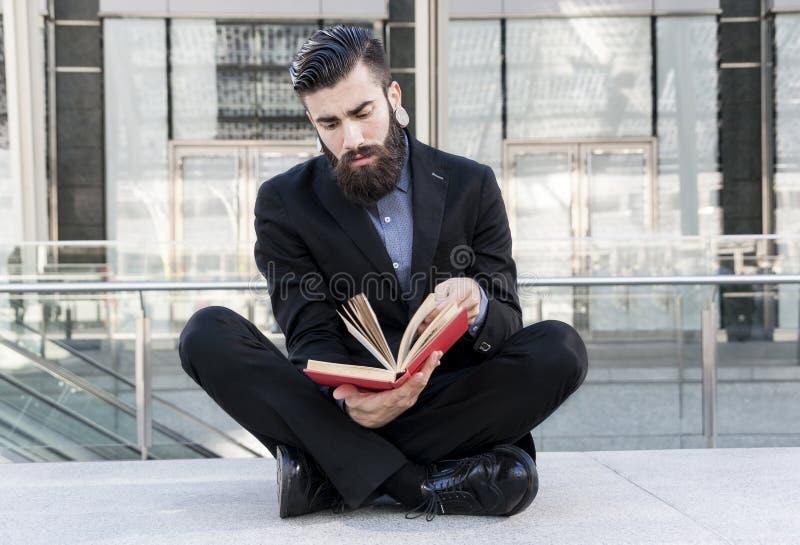 Jeune hippie lisant un livre se reposant dehors photographie stock