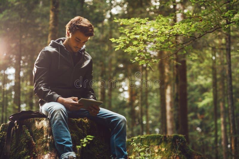 Jeune homme à l'aide d'un comprimé numérique dans les bois image stock