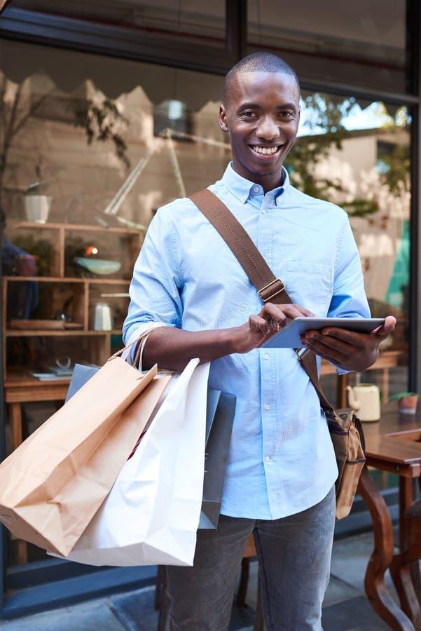 Jeune homme à l'aide d'un comprimé tout en faisant des emplettes dans la ville image stock