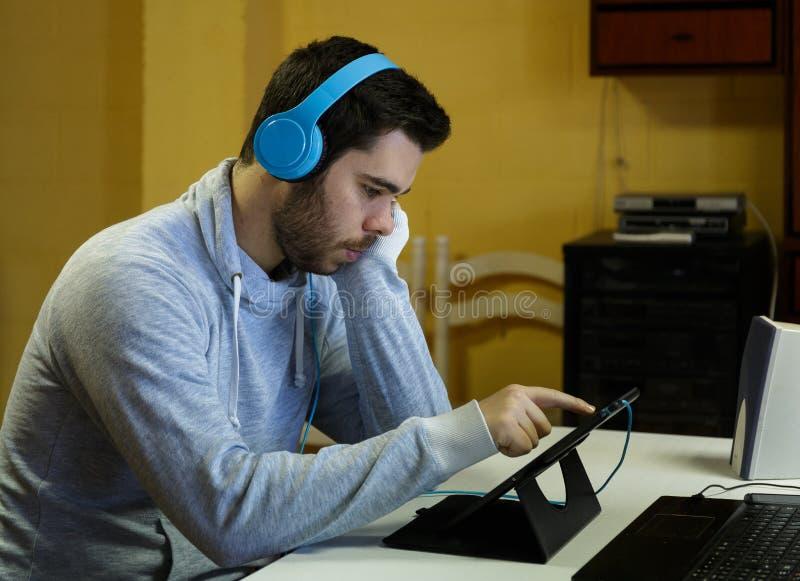 Jeune homme à l'aide de son mobile, comprimé, ordinateur portable et écouteurs images libres de droits