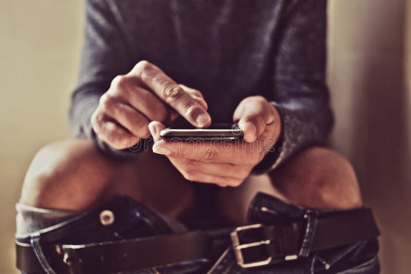Jeune homme à l'aide de son smartphone dans la toilette photo stock