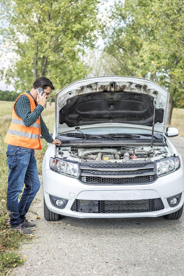 Jeune homme à l'aide de son téléphone portable devant une voiture décomposée photos stock