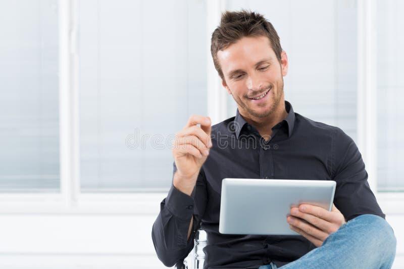 Jeune homme à l'aide du comprimé de Digital photo stock