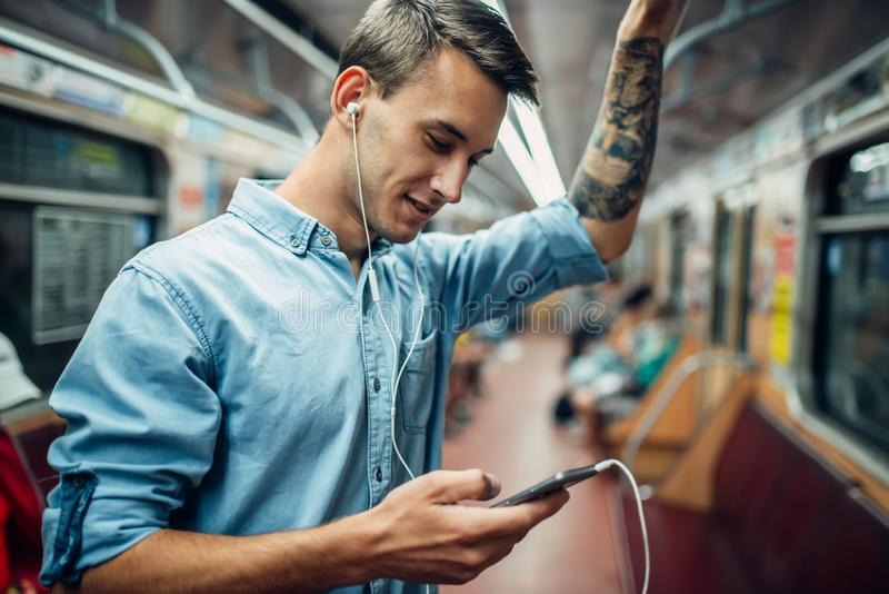 Jeune homme à l'aide du téléphone dans la métro, personnes dépendantes images libres de droits