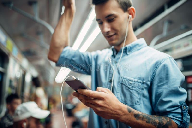 Jeune homme à l'aide du téléphone dans le souterrain, dépendance photos libres de droits