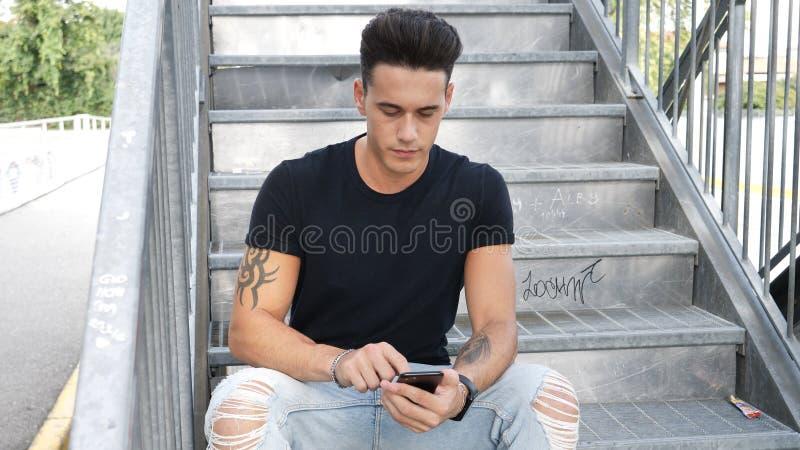 Jeune homme à l'aide du téléphone portable dehors dans l'environnement urbain photos stock