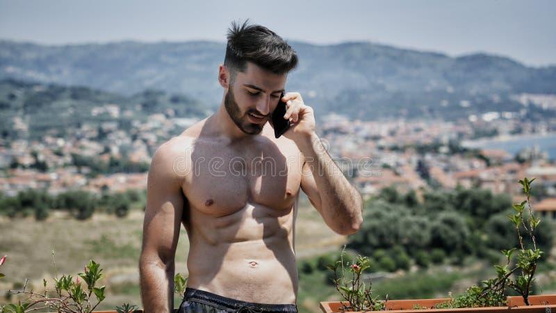 Jeune homme à l'aide du téléphone portable pour appeler quelqu'un image stock