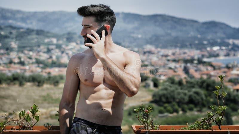 Jeune homme à l'aide du téléphone portable pour appeler quelqu'un photo stock