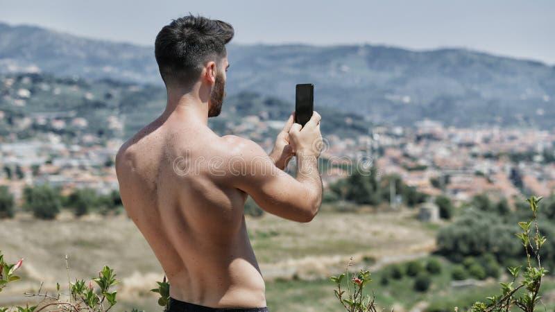 Jeune homme à l'aide du téléphone portable pour filmer le paysage images stock