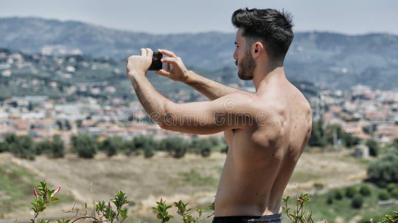 Jeune homme à l'aide du téléphone portable pour filmer le paysage photos libres de droits