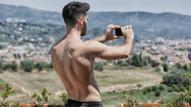 Jeune homme à l'aide du téléphone portable pour filmer le paysage photographie stock