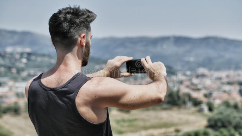 Jeune homme à l'aide du téléphone portable pour prendre des photos de paysage photos stock