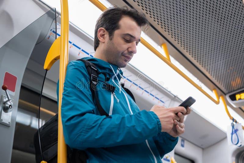 Jeune homme à l'aide du téléphone portable sur le souterrain photos libres de droits