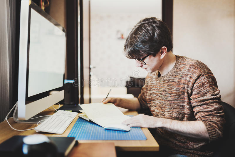 Jeune homme à la maison utilisant un ordinateur photo libre de droits