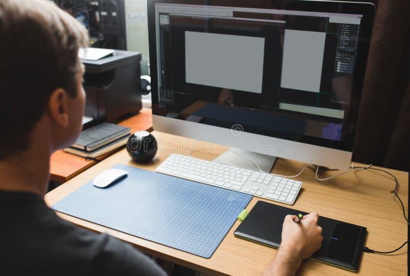 Jeune homme à la maison utilisant un ordinateur, un promoteur indépendant ou un fonctionnement de concepteur images stock