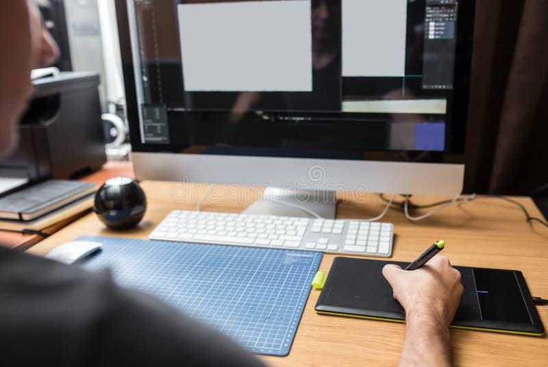 Jeune homme à la maison utilisant un ordinateur, un promoteur indépendant ou un fonctionnement de concepteur images libres de droits