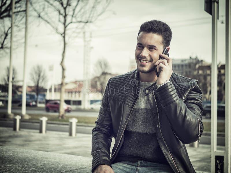 Jeune homme à la mode beau talkiing au téléphone portable photos stock