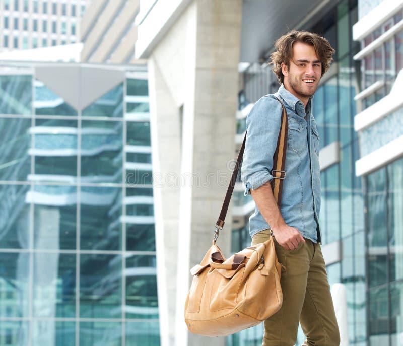 Jeune homme à la mode souriant avec le sac de voyage photos stock