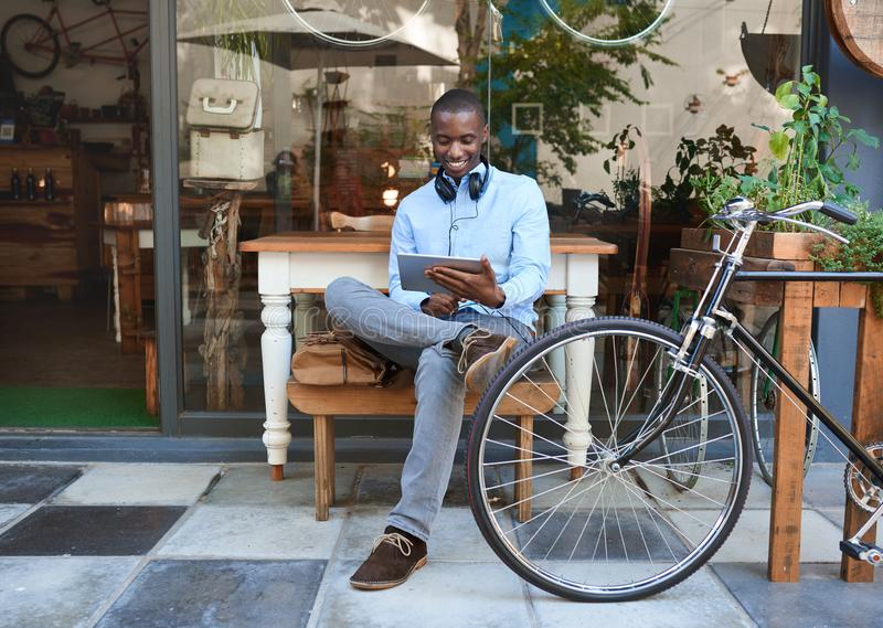 Jeune homme à la mode surfant le filet à un café de trottoir images libres de droits