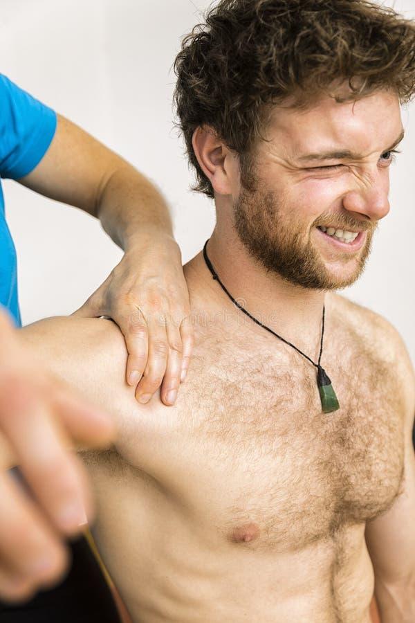 Jeune homme à la physio- thérapie avec douleur images stock
