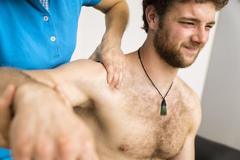 Jeune homme à la physio- thérapie avec douleur photographie stock libre de droits