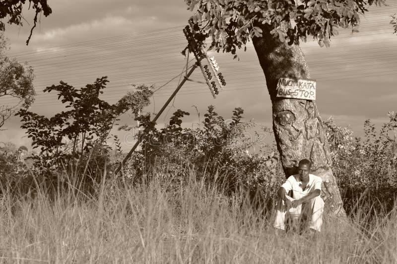 Jeune homme à un arrêt d'autobus au Zimbabwe rural, Afrique image stock