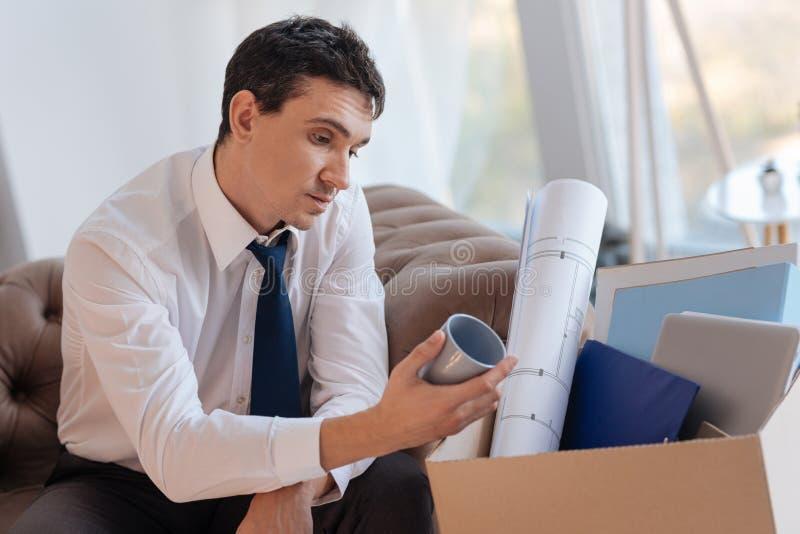 Jeune homme écarté reposant et regardant sa tasse bleue préférée photos stock