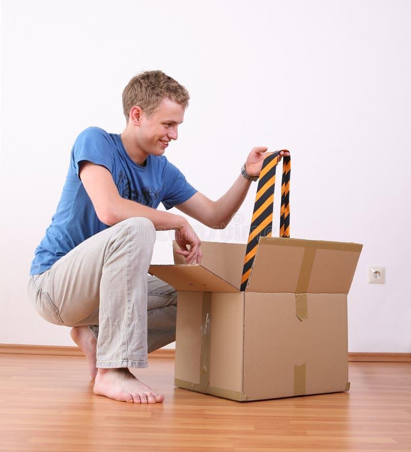 Jeune homme éclatant la boîte en carton photo stock
