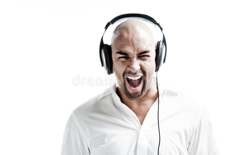 Jeune homme écoutant la musique bruyante et criant images stock