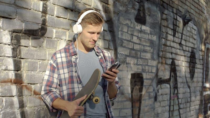 Jeune homme écoutant la musique et faisant défiler sur le téléphone portable, tenant la planche à roulettes photo stock