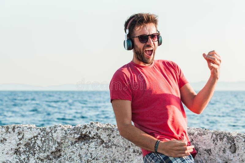 Jeune homme écoutant la musique sur des écouteurs jouant la guitare imaginaire images libres de droits