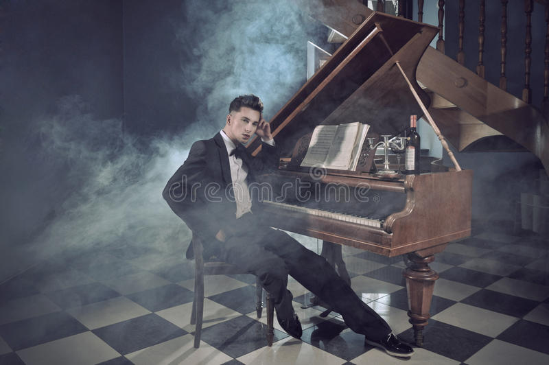 Jeune homme élégant avec le piano photos stock
