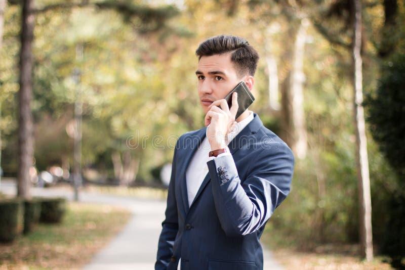 Jeune homme élégant avec le smartphone en parc photo libre de droits