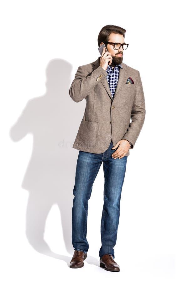jeune homme élégant avec une barbe, habillée dans un studio sur un blanc photo stock