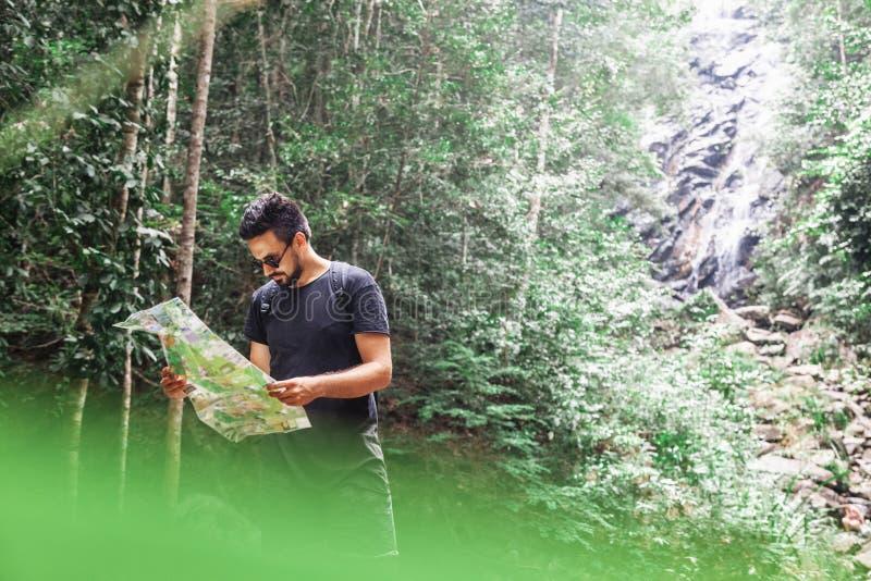 Jeune homme élégant beau de métis dans un T-shirt noir avec une carte du secteur dans des ses mains dans la jungle, le trekking e photo stock