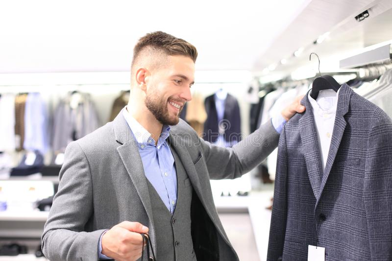 Jeune homme élégant choisissant le nouveau costume dans le magasin de mail ou d'habillement photos libres de droits