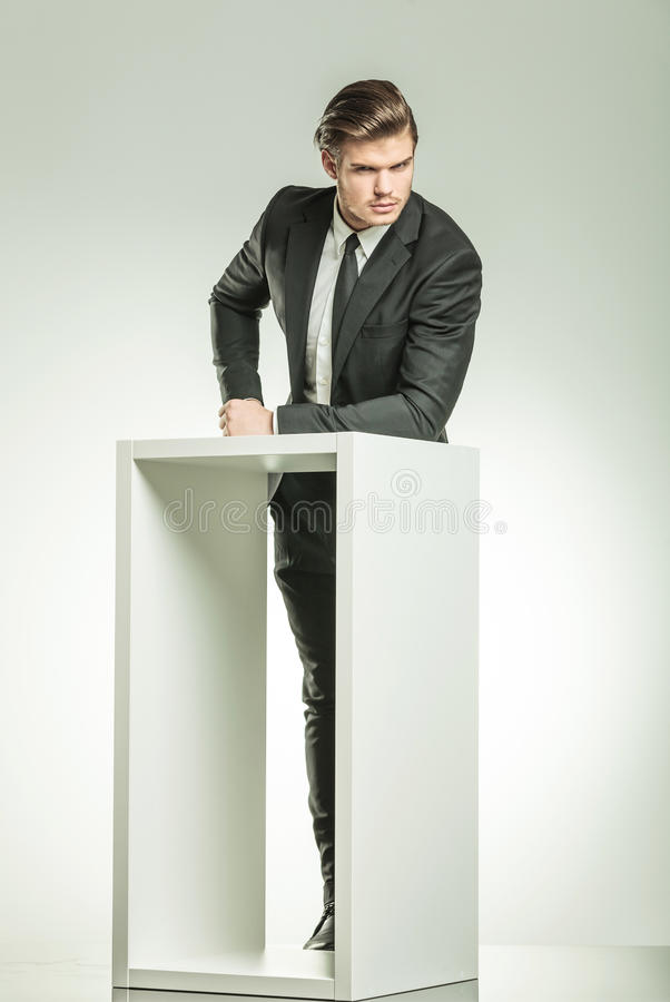 Jeune homme élégant d'affaires se reposant sur une table image stock