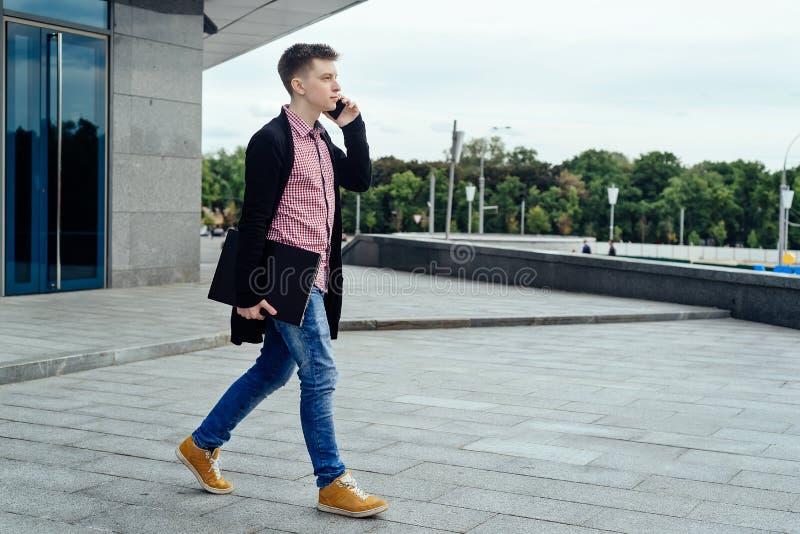 Jeune homme élégant dans la chemise et des jeans de plaid avec l'ordinateur portable photographie stock