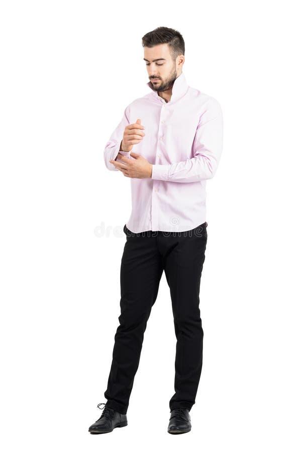 Jeune homme élégant dans la chemise rose boutonnant ses douilles photographie stock libre de droits