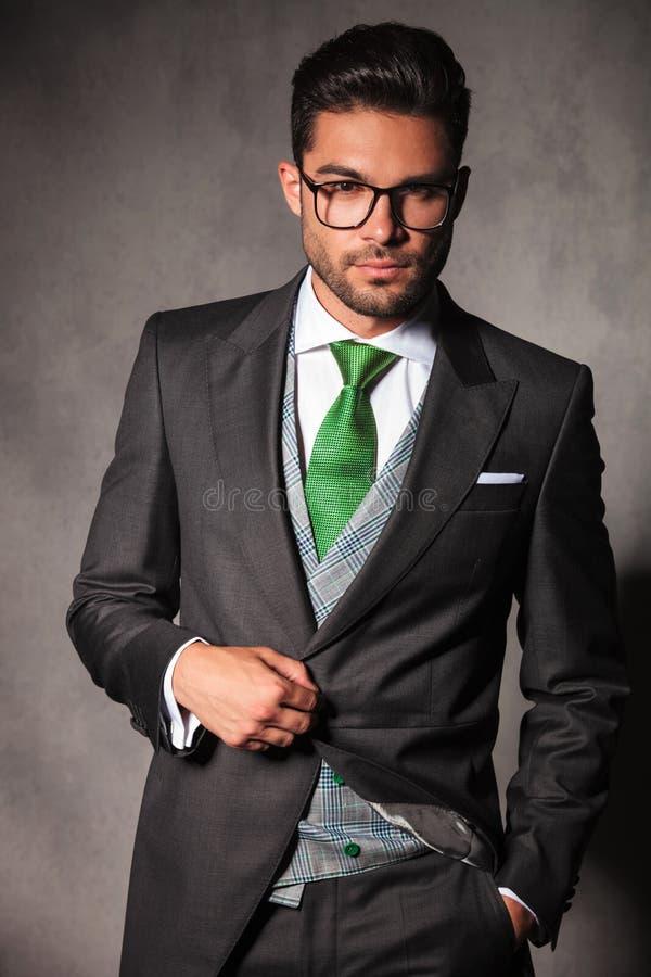 Jeune homme élégant dans la veste de smoking tenant le bouton photos libres de droits