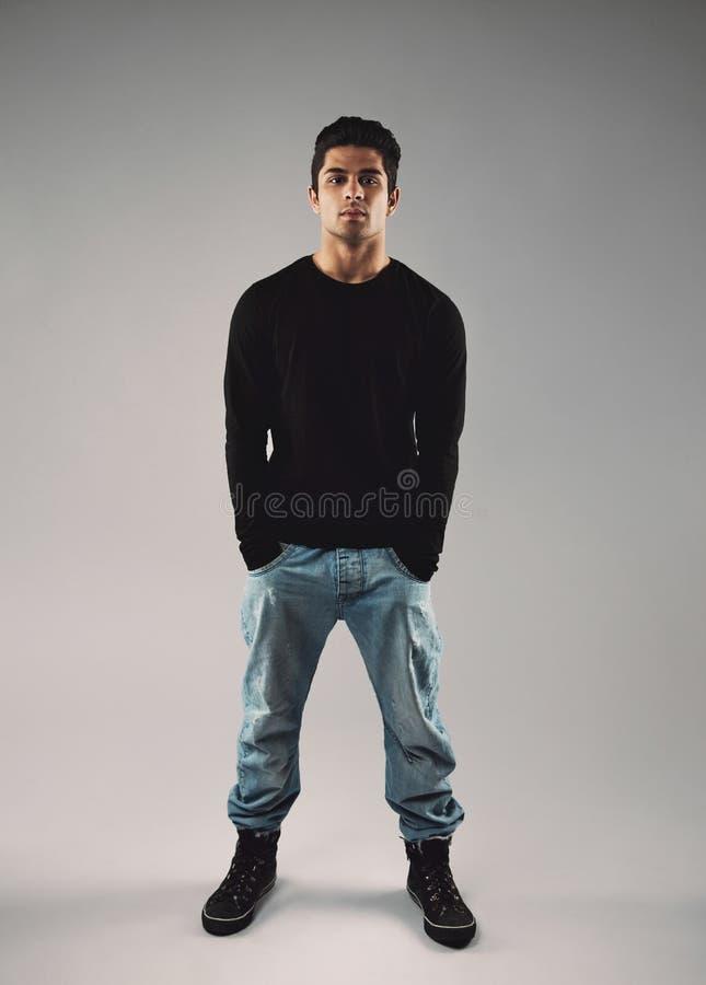 Jeune homme élégant dans les vêtements sport sur le fond gris photo libre de droits