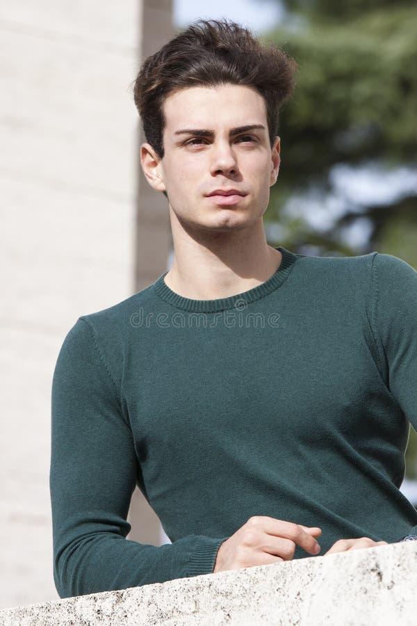 Jeune homme élégant de cheveux dehors sur le rebord, knit serré photo libre de droits